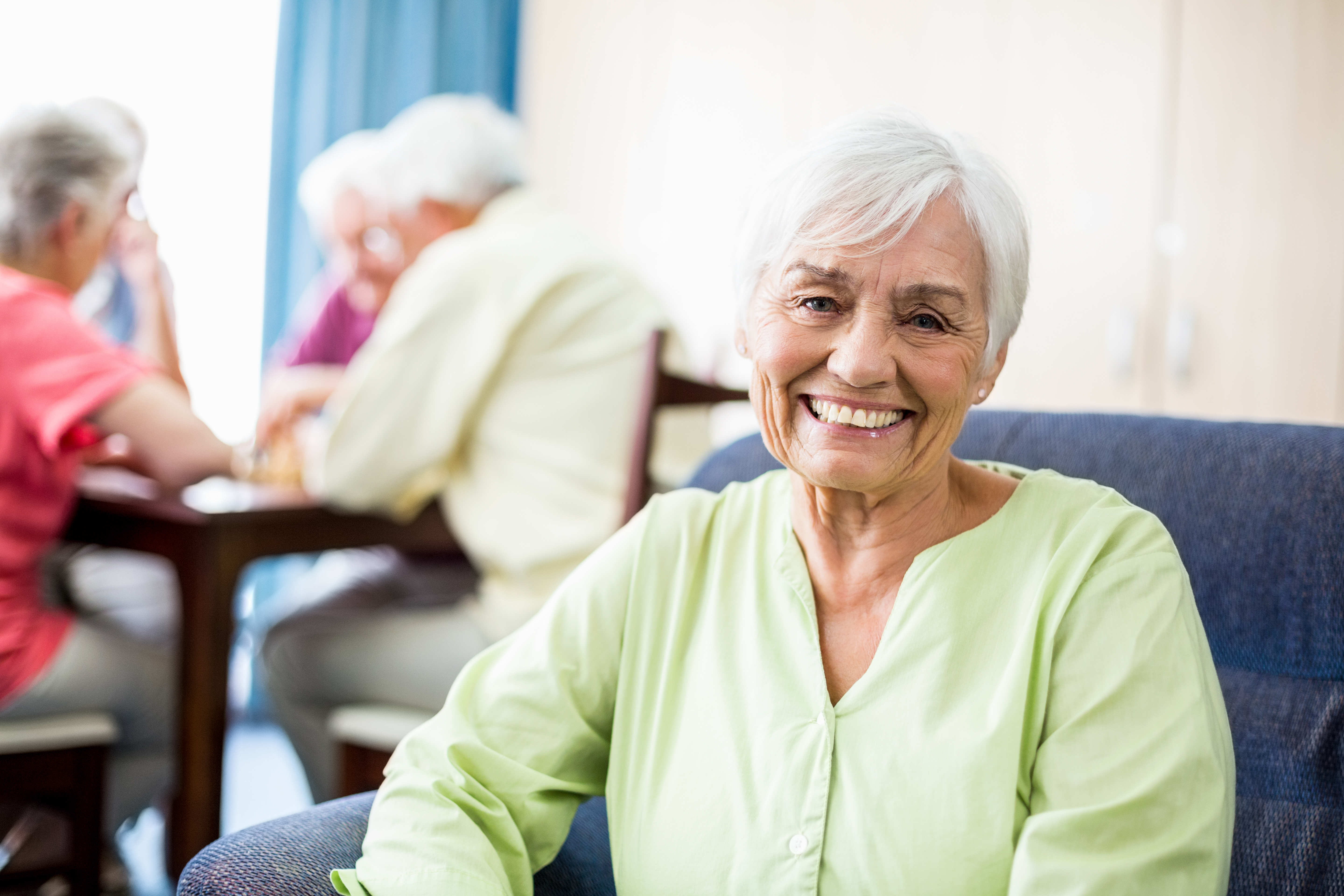 senior woman seated looking at viewer with other aged people in the backgroubd