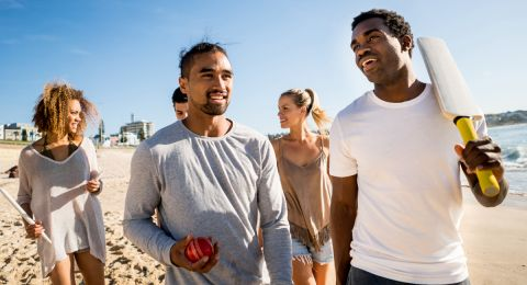 Group of young people from diverse ethnicities walking along an Australian beach with a cricket bat